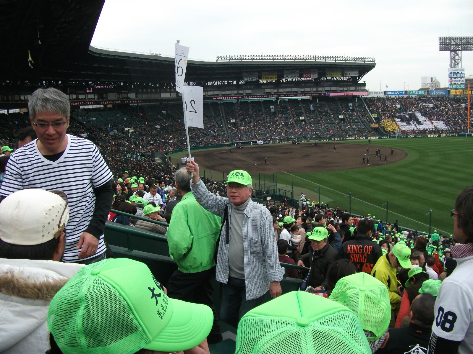 大高vs平安の大試合直前に26回卒の招集を促すために26回卒の旗をかざして1塁側アルプススタンド入りする末吉。 何から何まで偉い!!